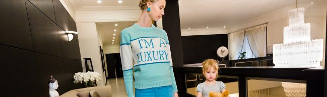 """Eine junge Mutter steht neben ihrer Tochter in einem edel eingerichteten Haus. Auf dem Pullover der Mutter steht """"I'm a Luxury"""""""