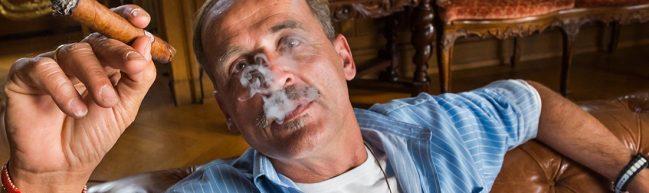 Florian Homm sitzt auf einem Sofa und bläst den Rauch einer Zigarre in die Kamera.
