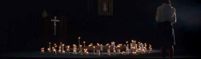Eine nackte Frau liegt auf dem Boden, umringt von dutzenden brennenden Kerzen. Im Hintergrund steht ein Kreuz, im Vordergrund eine Frau mit dem Rücken zur Kamera.