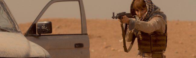 Sam steht neben einem Auto. Sie zielt mit einem Maschinengewehr auf etwas außerhalb des Bildes.
