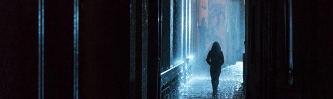 Dunkle Straße, Regen im Schlaglicht, eine dunkle Gestalt geht über Kopfsteinpflaster