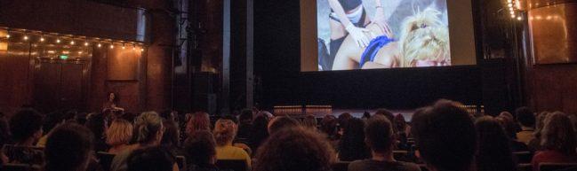 Ein voller Theatersaal. Auf der Leinwand eine Sexszene zwischen zwei Frauen.