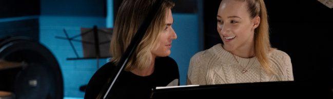 Stig (Luke Eisner) und Jodi (Ava Michelle) sitzen gemeinsam an einem schwarzen Flügel. Sie lachen einander an.
