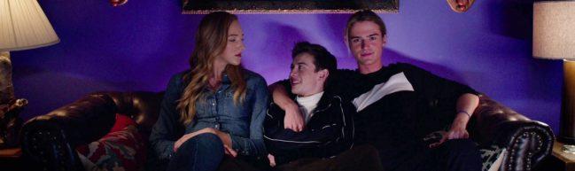 Stig (Luke Eisner) und Jodi (Ava Michelle) sitzen auf einem Sofa, zwischen ihnen sitzt Jack (Griffin Gluck). Jodi schaut Jack böse an, während Stig seinen Arm freundschaftlich um ihn gelegt hat.