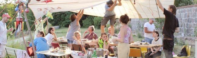 Eine Gartenparty. Menschen sitzen an gedeckten Tischen.