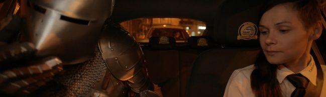 Aufnahme der Taxifahrerin Ljiljana und ihres Beifahrers in Ritterrüstung durch die Frontscheibe des Taxis