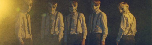 Die fünf Protagonist:innen stehen mit ihren Masken in einem nebligen Licht und starren direkt in die Kamera.