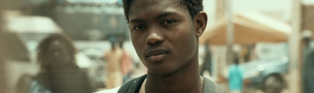 Ein junger Mann blickt mit leichtem Lächeln geradeaus.