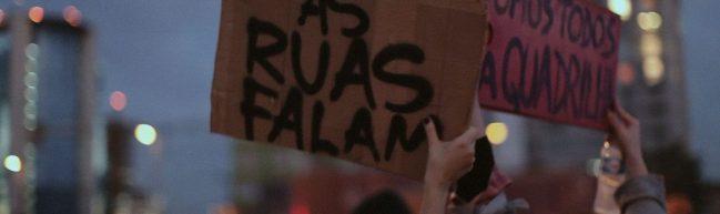"""Handgemalte Schilder bei einer Demonstration. Im Vordergrund """"as ruas falam"""""""