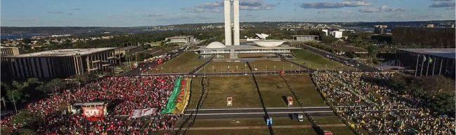 Luftaufnahme von zwei Demonstrationen vor dem brasilianischen Parlament. Die Demonstrationen sind durch mehrere Absperrungen voneinander getrennt.
