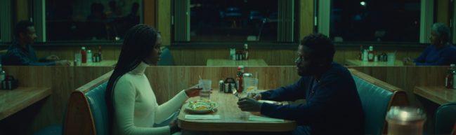 Queen & Slim sitzen in einem schummrigen Restaurant.