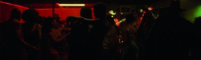 Ein Nachtclub. Das Licht ist sehr dunkel und wir können nur die Umrisse tanzender Körper erkennen.