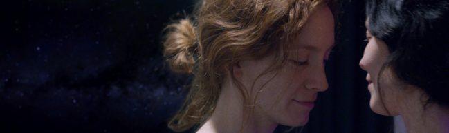 Mimaroben (Emelie Jonsson) und Isagel (Bianca Cruzeiro) lächeln einander an, im Hintergrund Weltraum