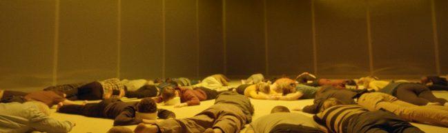 Mehrere Personen liegen mit dem Gesicht nach unten in einem gelblich beleuchteten Raum