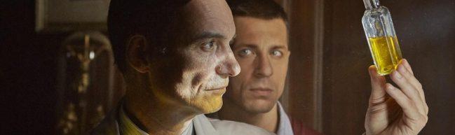Mikolášek mit einem Glasfläschcen, das mit Urin gefüllt ist. Er hält es ins Licht und betrachtet es. Hinter ihm steht Palko und und blickt ihn an.