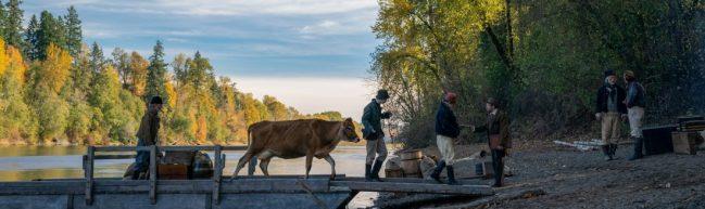 Die Kuh ist da: Eine Kuh läuft über einen Holzsteg an Land. Am Flussufer und Waldrand stehen Männer in Kleidung des 19. Jahrhunderts.