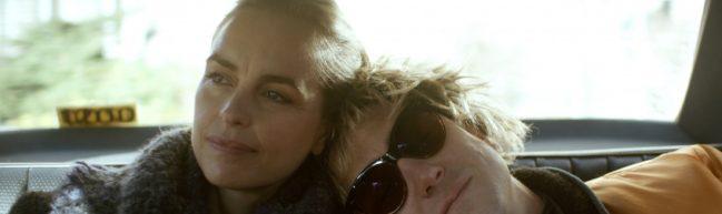 Lisa und Sven auf der Rückbank eines Taxis. Lars trägt eine Sonnenbrille und eine Perücke. Er lehnt sich an die Schulter von seinem Schwesterlein