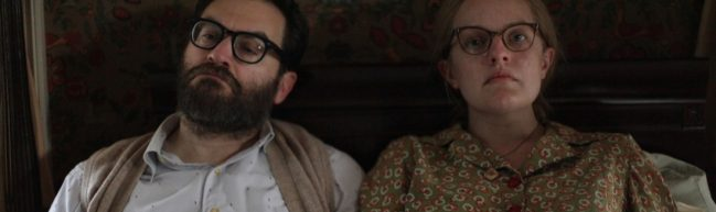 Stanley und Shirley sitzen nebeneinander im Bett. Sie schauen sich nicht an und machen ernste Gesichter.