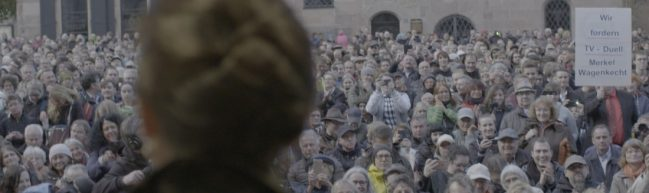 Eine Menschenmenge und Sahra Wagenknechts Hinterkopf.