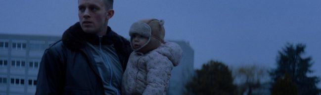 Andi mit seiner kleinen Tochter auf dem Arm. Im Hintergrund ein Hochhaus.