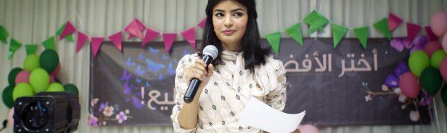 Maryam mit einem Mikrofon und einem Zettel, von dem sie ihre Reden abliest. Im Hintergrund die farbenfrohe Dekoration einer Feier.