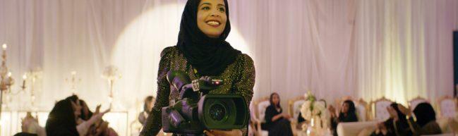 Salma in einem festlichen Kleid hinter einer Videokamera. Sie lacht strahlend. Im Hintergrund eine Hochzeitsgesellschaft.