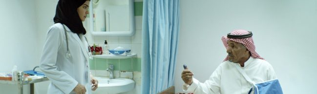 Maryam im Krankenhaus. Sie trägt einen weißen Kittel und ein schwarzes Kopftuch. Ihr Patient, ein älterer Mann, sitzt neben ihr und zeigt ihr seinen dunklen Daumen.