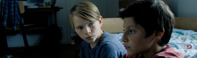 Ben (Yoran Leicher) und Tariq (Sobhi Awad) sitzen nebeneinander in einem Kinderzimmer, Ben schaut Tariq an, Tariq blickt ins Leere