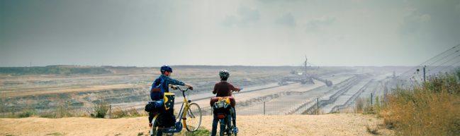 Zu Weit Weg: Zwei Kinder mit Fahrrädern stehen vor einer Grube des Braunkohleabbaus