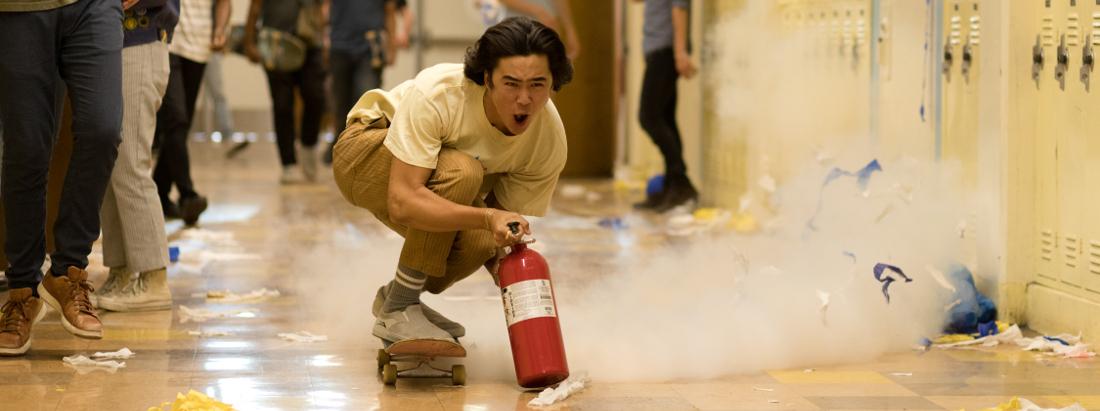 Ein Schüler skatet durch einen Schulflur. Dabei benutzt er einen Feuerlöscher zum Antrieb.
