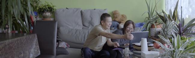 Bay und Tam sitzen auf dem Sofa ihres Wohnzimmers und skypen.