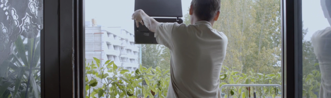 Tam zeigt durch den Laptop sein selbst angebautes Gemüse