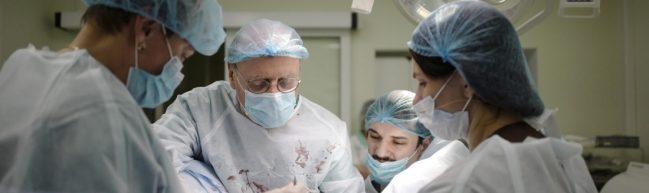 Vier Personen operieren im Operationssaal, die weißen Kittel sind blutbespritzt.