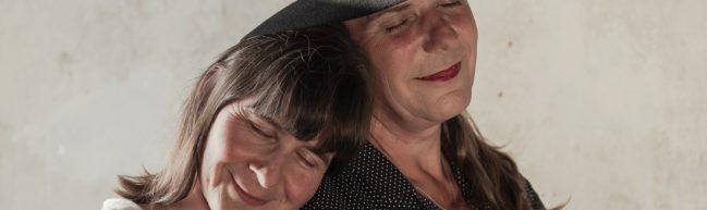 Elisabeths Partnerin lehnt sich an Elisabeths Schulter, beide lächeln mit geschlossenen Augen.